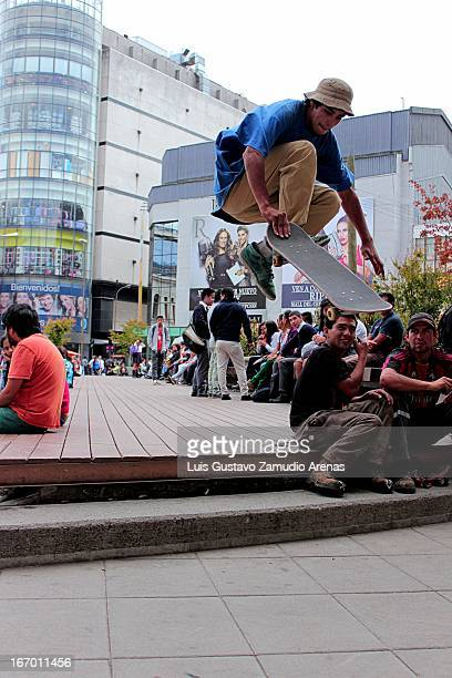 CONTENT] Skateboarder jumping below the Concepcions Tribunal Center while a couple of workers are whatching him