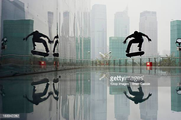 a skateboarder mid-air in a downtown area - symmetry stock pictures, royalty-free photos & images