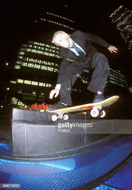 Skateboarder ollie in inner city at night wearing suit and tie Dundee UK 2000s