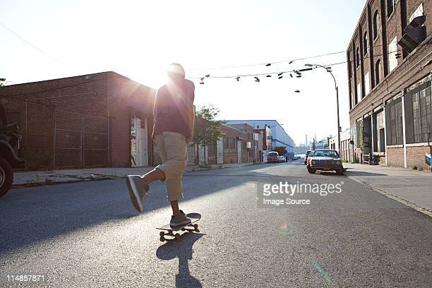 Skateboarder on urban street in sunlight