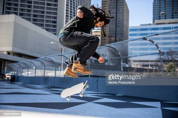 skateboarder performing trick in downtown atlanta - skating stock pictures, royalty-free photos & images