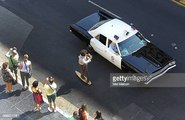 A skateboarder photographs a 1972 AMC Matador vehicle as it travels along Hollywood Blvd in Hollywood during the annual 104 Day Parade a salute to...