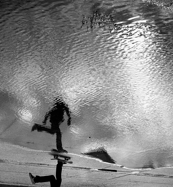 Skateboarder reflection in puddle