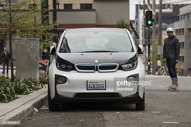 A skateboarder rides near a Bayerische Motoren Werke AGb i3 electric vehicle part of the ReachNow carshare program parked in Seattle Washington US on...