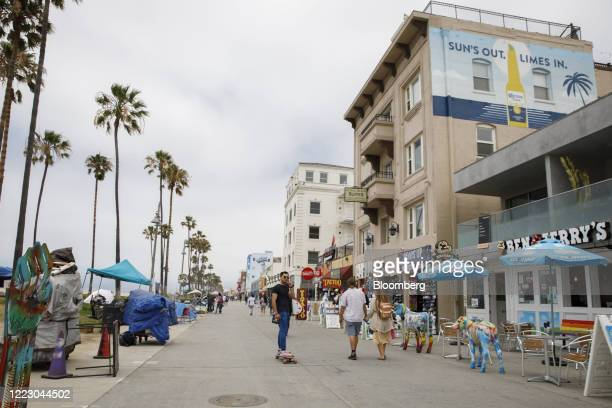 Skateboarder rides through Venice Beach in Los Angeles, California, U.S., on Friday, June 26, 2020. California reported 5,349 new cases, its...