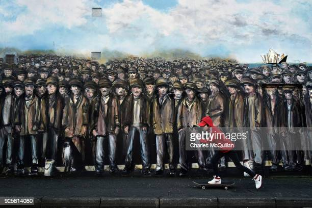 A skateboarder skates past a mural depicting Belfast shipyard workers near Sandy Row on March 1 2018 in Belfast Northern Ireland The Titanic workers...