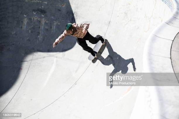 skateboarder skating empty pool in skatepark - elevated view stock pictures, royalty-free photos & images