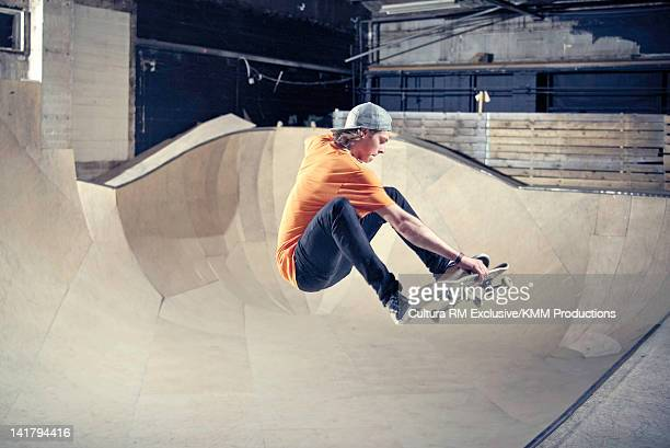 Skateboarder skating on indoor ramp