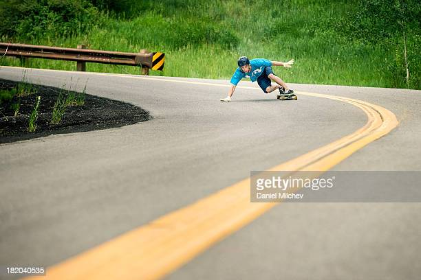 Skateboarder taking a sharp turn with high speed.