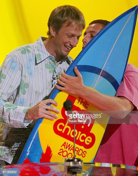 Skateboarder Tony Hawk congratulates actor Adam Sandler after winning the 'Choice' award for 'Best Actor Comedy' on stage at The 2004 Teen Choice...