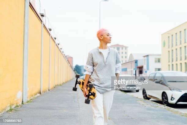 skateboarder walking along sidewalk - capelli corti foto e immagini stock