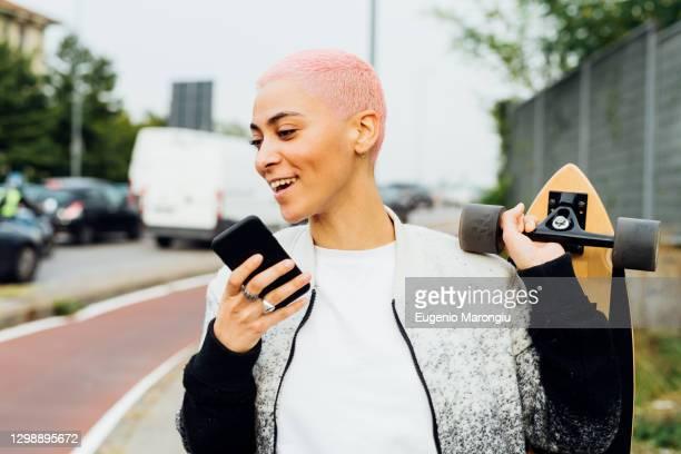 skateboarder walking and using cellphone - capelli corti foto e immagini stock