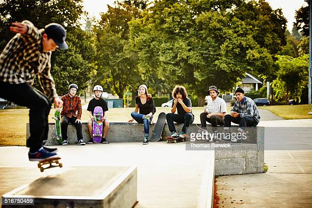 Skateboarders hanging out watching friend skate