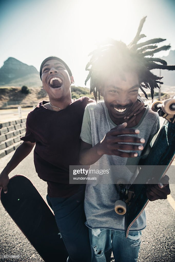 Skateboarders Laugh Together, Outside, With Skateboards in Hand : Stock Photo