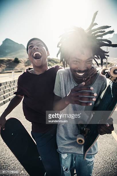 Skateboarders Laugh Together, Outside, With Skateboards in Hand