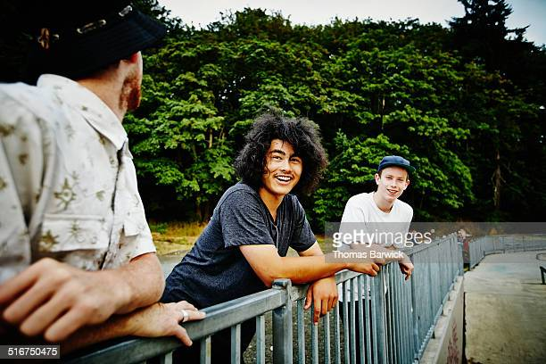 Skateboarders leaning on fence around skate park