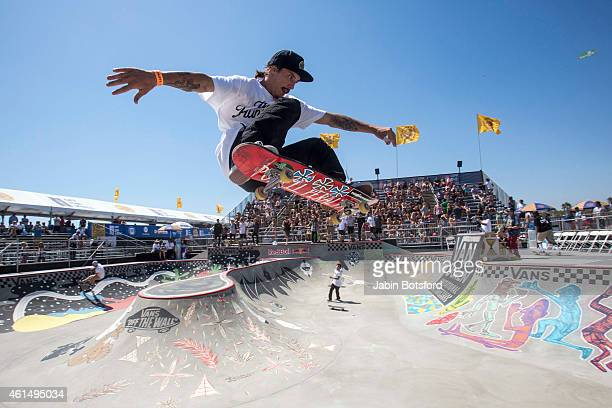 Skateboarders practice in the Vans Pro Bowl as fans watch during the 6th day of the Vans US Open at the Huntington Beach Pier in Huntington Beach on...