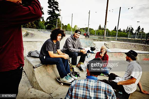 Skateboarders sitting in discussion in skate park