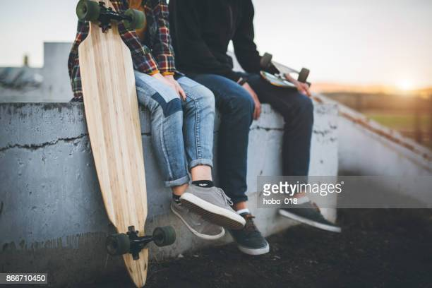 skateboarders taking a rest in skate park - skating stock pictures, royalty-free photos & images