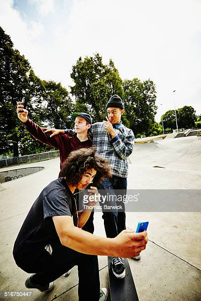 Skateboarders taking self portraits in skate park