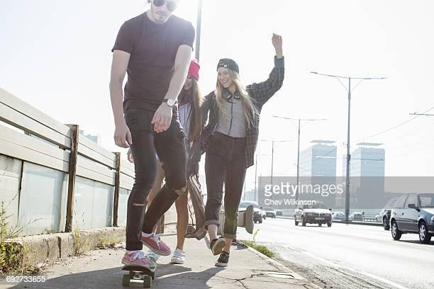 Skateboarders walking and skateboarding together on street, Budapest, Hungary