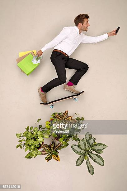 Skateboarding bussinessman in nature with shopping bags and smartphone