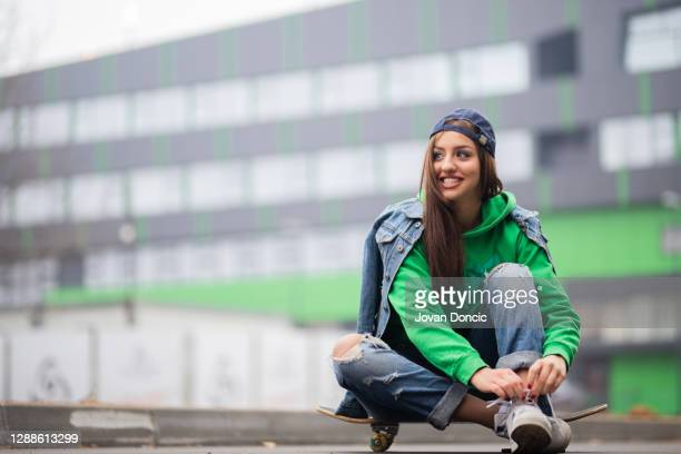 skateboarding girl tiying her shoelaces - lace glove stock pictures, royalty-free photos & images