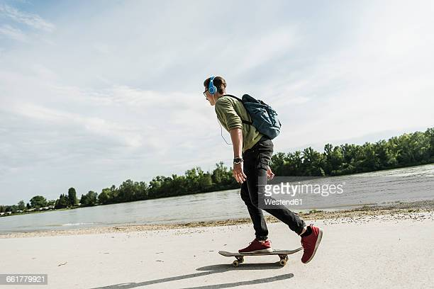 Skateboarding young man with headphones
