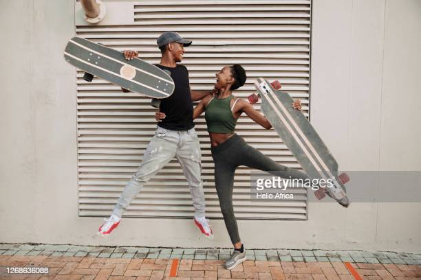 skater couple jumping with skateboards in hand - africa stock pictures, royalty-free photos & images