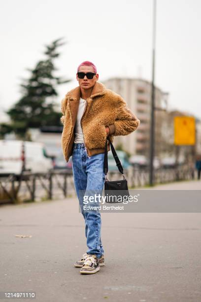 Skater Evan Mock wears sunglasses a brown fluffy jacket a white tshirt blue denim jeans pants Nike sneakers shoes a Prada black bag outside Balmain...