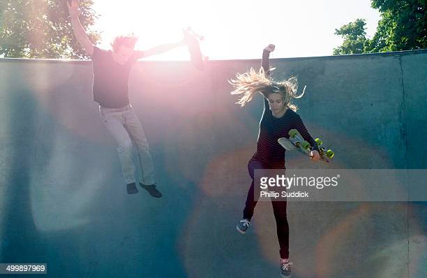 Skater girl and Boy jumping down a ramp together