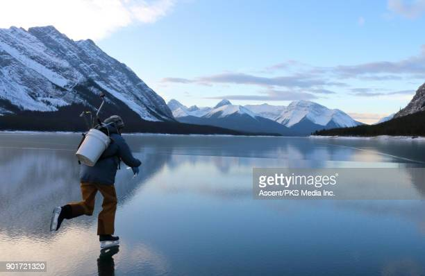 Skater heads out to ice fish on mountain lake