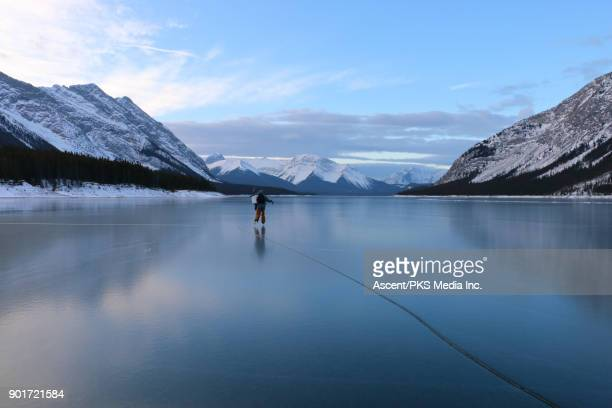 skater heads out to ice fish on mountain lake - winter sport stock pictures, royalty-free photos & images