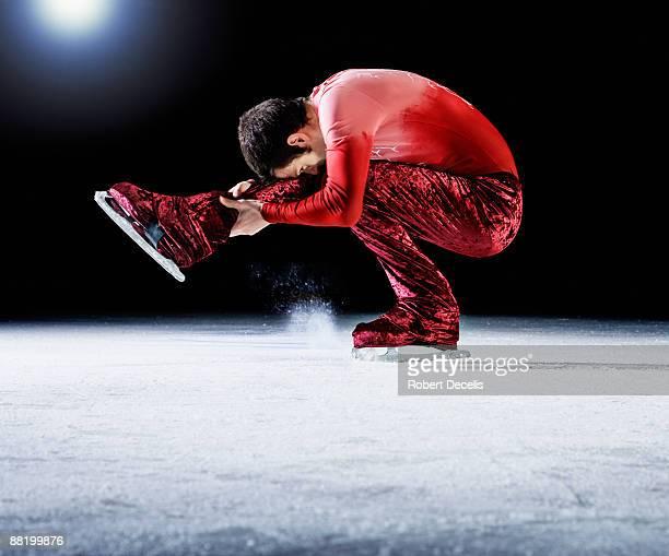 "skater performing a ""sit spin"". - patinage artistique photos et images de collection"
