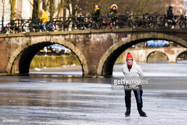 TOPSHOT A skater skates on the ice of the lightly frozen Keizersgracht Canal in Amsterdam on March 1 2018 Heavy snowfall and deadly blizzards lashed...