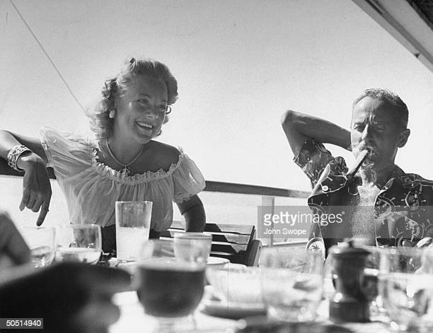 Skater Sonia Henie wearing peasant blouse while sitting next to cigarpuffing producer Darryl Zanuck while vacationing a Eden Roc on the French Riviera