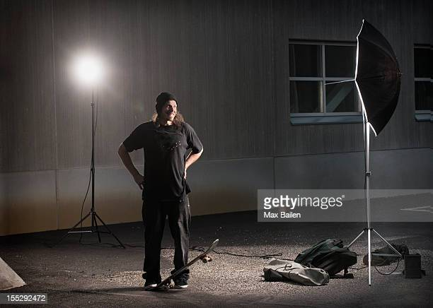 Skater standing under photo lights