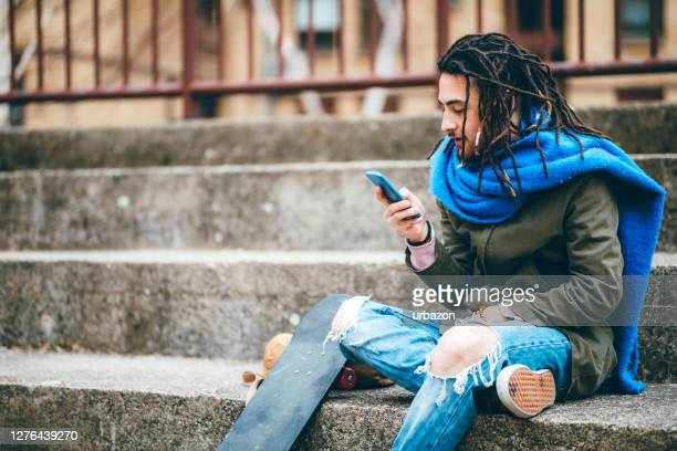 skater texting or checking social media on phone - borough district type stock pictures, royalty-free photos & images