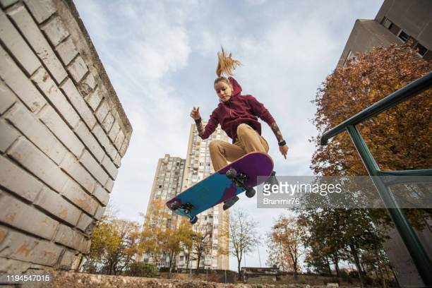 skater woman jumping on her skate. - stunt stock pictures, royalty-free photos & images
