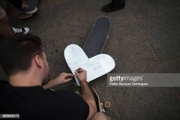 A skater writes a message on a heart shape skateboard during a vigil in tribute to Ignacio Echavarria a victim of the London terror attack outside of...