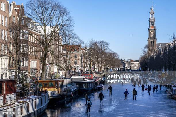Skaters gather on ice on the canals in Prinsengracht, Amsterdam on February 13 as municipal authorities called on residents to go skating in their...