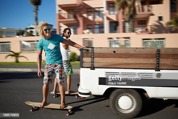 Skaters hanging on to car while riding longboards