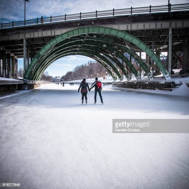 Skaters holding hands and skating under a bridge on the Rideau Canal for Winterlude