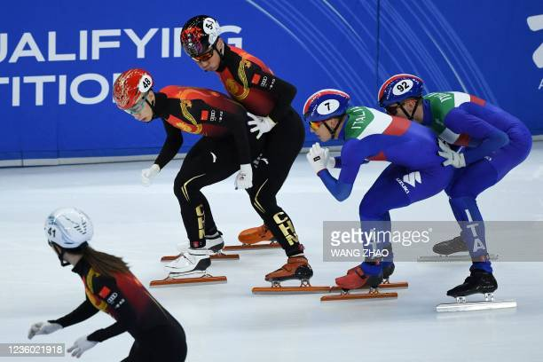Skaters of Italy compete in the mixed team relay quarter finals during the 2021/2022 ISU World Cup short track speed skating, part of a 2022 Beijing...