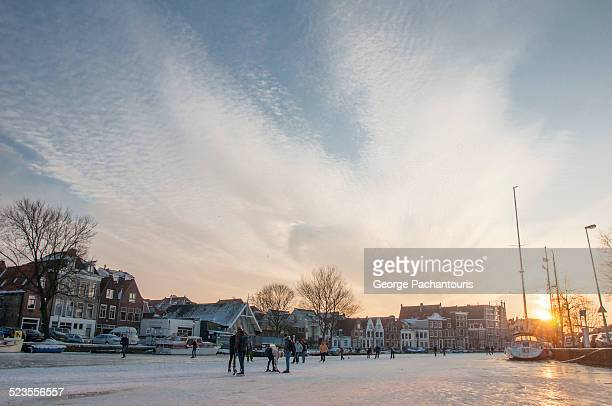 Skaters on frozen river in Haarlem
