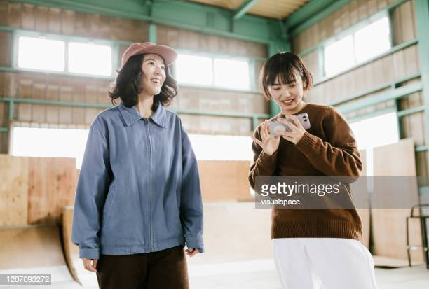 skaters streaming skateboard videos from smartphone - adult videos japan stock pictures, royalty-free photos & images