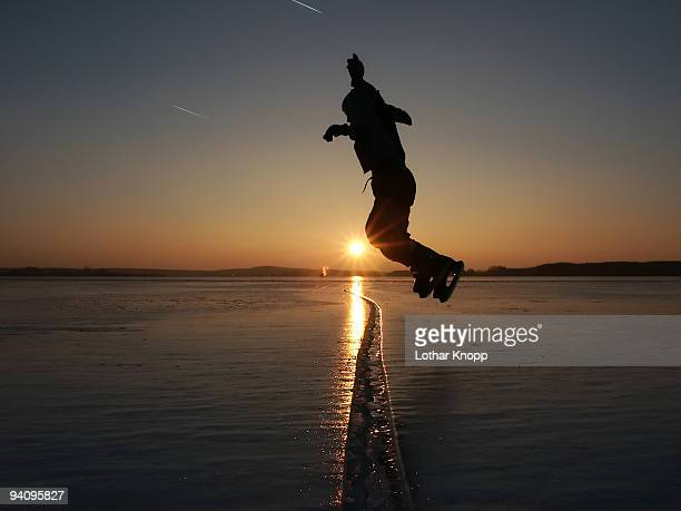 Skating boy jumping over a crack in the ice