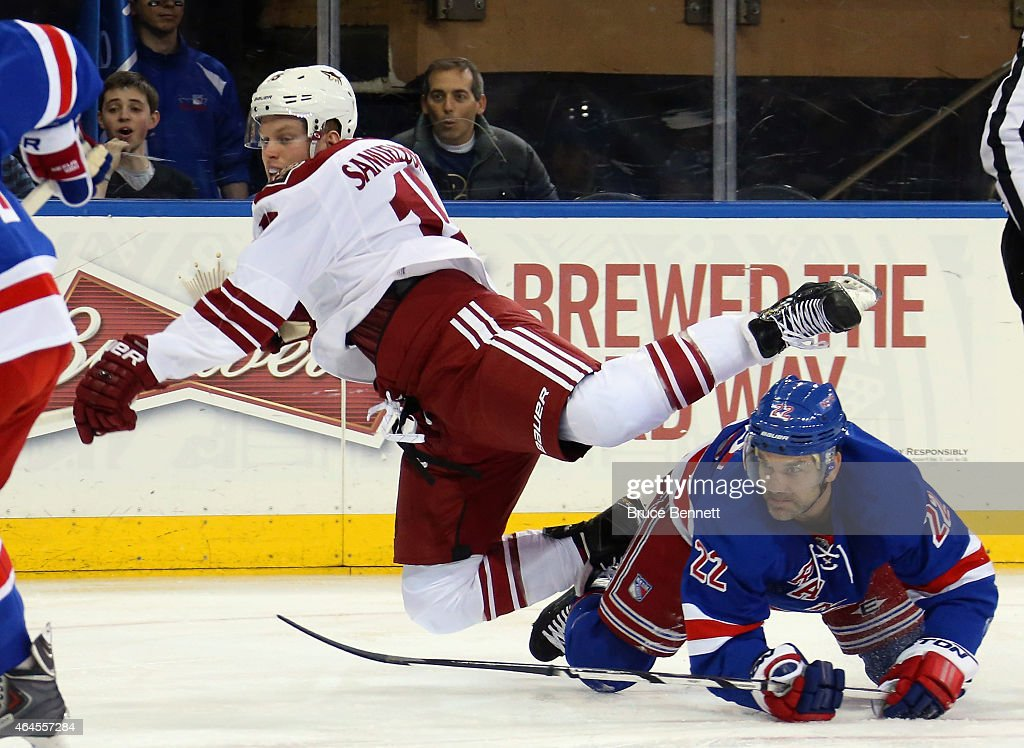 Skating in his first NHL game, Henrik Samuelsson #15 of the Arizona Coyotes is tripped up by Dan Boyle #22 of the New York Rangers at Madison Square Garden on February 26, 2015 in New York City.
