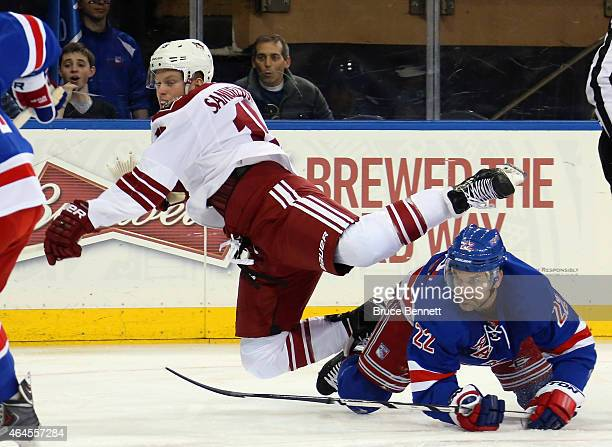 Skating in his first NHL game Henrik Samuelsson of the Arizona Coyotes is tripped up by Dan Boyle of the New York Rangers at Madison Square Garden on...