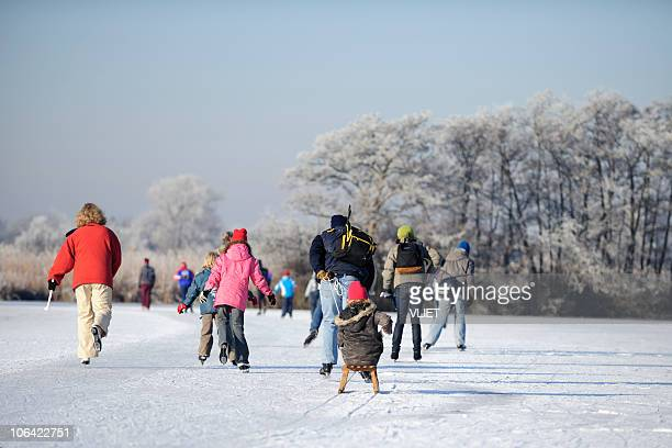skating people on a lake in the netherlands - skating stock photos and pictures